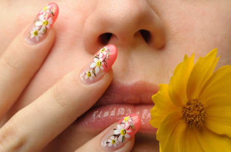 Female face close up c flower in a mouth and nail art. Figure of camomiles on nails Stock Photo - 8131306