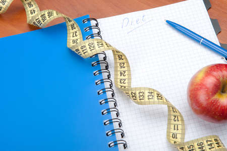 Planning of a diet. A notebook c an inscription - the Diet, a measuring tape, an apple and pen Stock Photo - 8131325