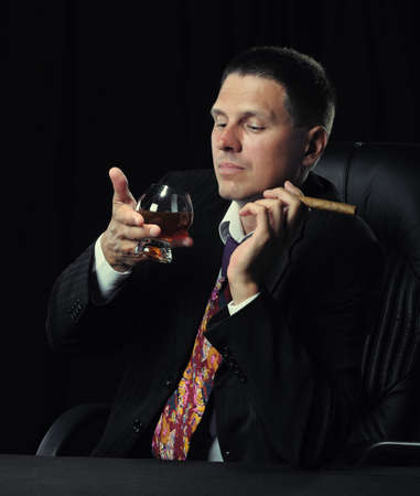 gangster background: The man with a cigar and a glass of cognac. A dark background