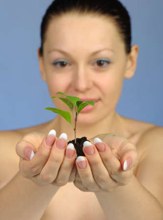 The woman holds in hands soil with a plant. Selective focus. A blue background photo