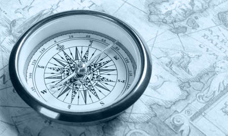 Old compass on ancient map. Blue toned image Stock Photo