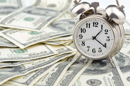 buying time: Time - money. Business concept. Analog hours on a heap of paper dollars