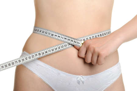 Female shapely a body and a measuring tape. It is isolated on a white background photo