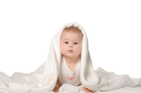 girl with towel: The baby under a towel. Age of 8 months. It is isolated on a white background Stock Photo