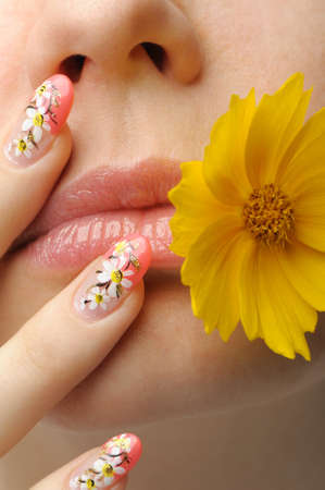 Female face close up c flower in a mouth and nail art. Figure of camomiles on nails Stock Photo - 8591035