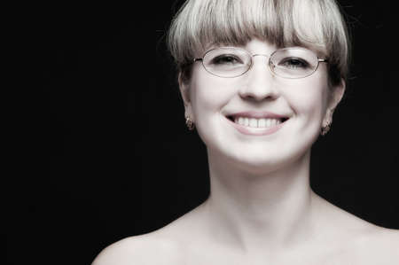 Portrait of the woman in eyeglasses close up. The bared shoulders. Toned image. photo
