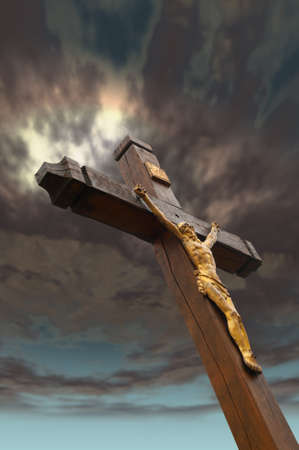 The crucifixion from a tree with Jesuss gilt figure. Drame sky photo
