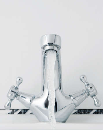 Water tap with a water stream. A bathroom with a white tile photo