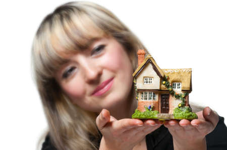 The business woman holds the small house in the hands. Focus on the house. It is isolated on the white background. Stock Photo - 9104927