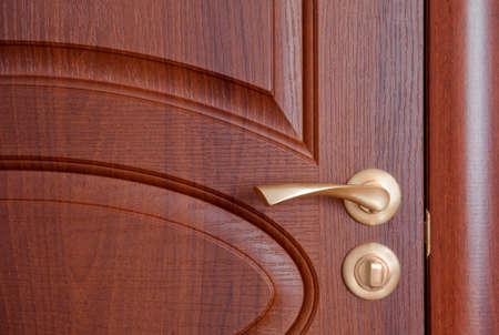 The door handle. A wooden door, brass handles. photo