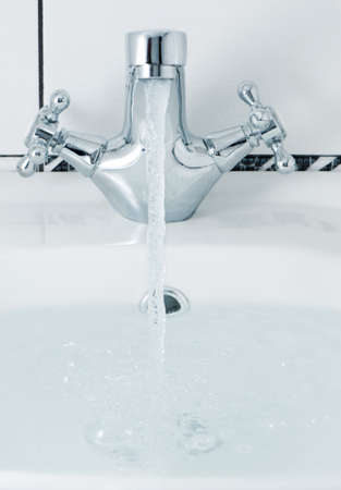 tap with a water stream. A bathroom with a white tile photo