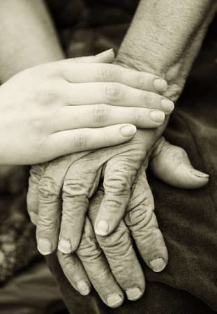 consoling: Old and young hands. Hands of the old woman - 84 years covered with young hands