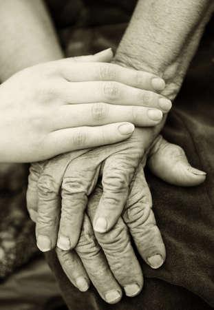 personas ayudando: Viejos y jóvenes manos. Manos de la anciana - 84 años cubiertos con las manos jóvenes