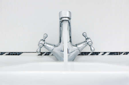 soppy: Water tap with a water stream. A bathroom with a white tile