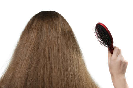 The girl with long hair and a hairbrush. The rear view. It is isolated on a white background photo