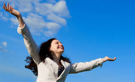 arms wide: La donna attraente felice con le mani sollevate. Contro il cielo blu Archivio Fotografico