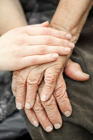 gentleness: Old and young hands. Hands of the old woman - 84 years covered with young hands
