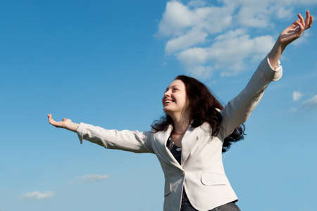 The happy attractive woman with the lifted hands. Against the blue sky photo