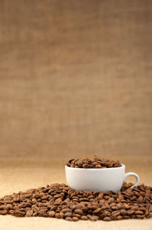 White cup with coffee grains. Grunge background Stock Photo - 9638016