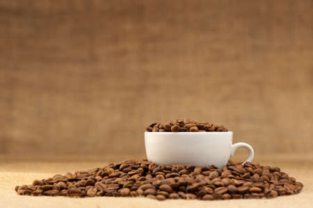 hot coffees: White cup with coffee grains. Grunge background Stock Photo