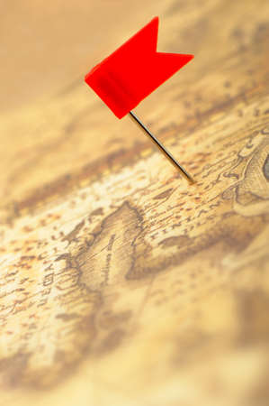 Flag red a pin on old map. Photo closeup. Selective focus photo