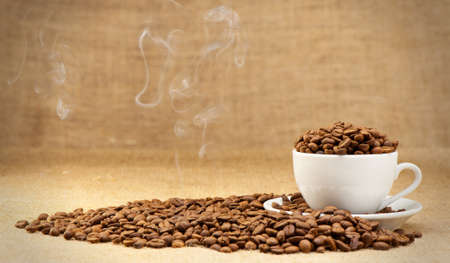 hot coffees: Cup with grains of coffee and a smoke. Grunge background Stock Photo