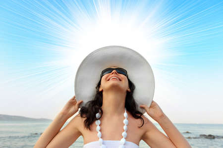 Portrait of the young woman in a hat. Sun beams behind photo