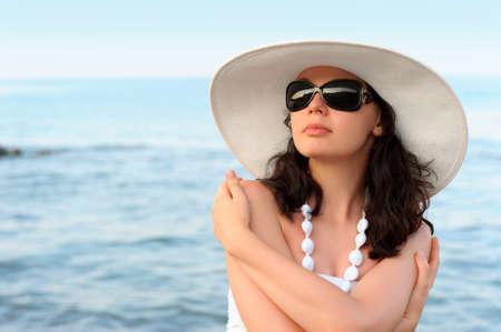 De vrouw op de zeekust. In zonnebril, een zomerjurk, een hoed. Stockfoto