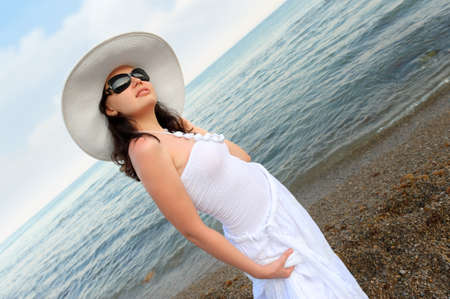 sundress: The woman on seacoast. In sun glasses, a sundress, a hat.