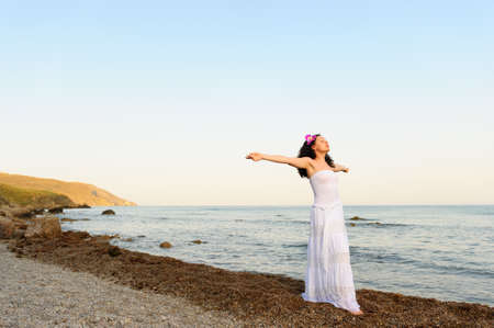 pardon: The woman in a white sundress on seacoast with open hands. A picturesque landscape
