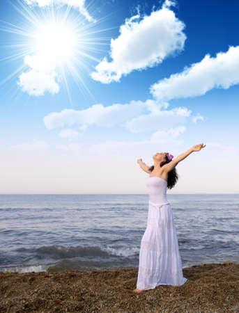 manos orando: La mujer en un vestido blanco de Costa con abrir manos. Cielo nuboso Foto de archivo