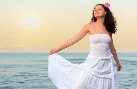 sundress: The woman in a white sundress on seacoast. Sunset illumination