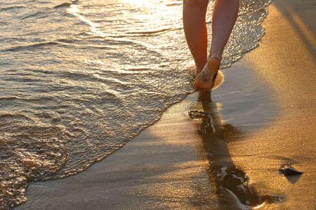 huella pie: huella en la arena. Puesta de sol de iluminaci�n, un fragmento de pies femeninos Foto de archivo