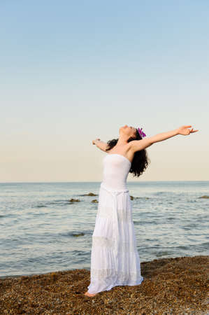 free photo: The woman in a white sundress on seacoast with open hands. A picturesque landscape