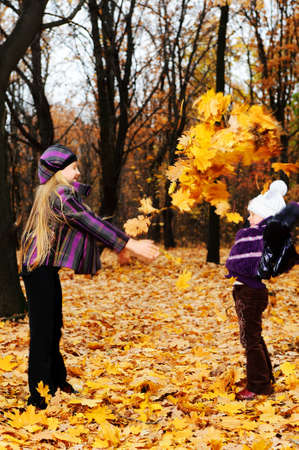 Children in autumn forest. Play fallen down leaf photo