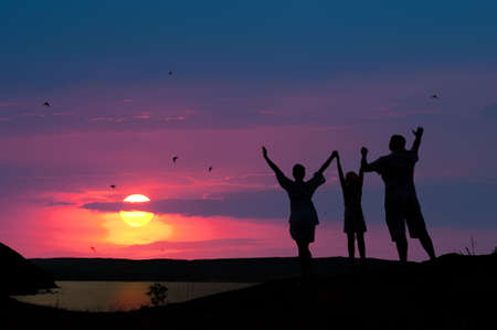The family from three persons welcomes the sunset sun. Stock Photo