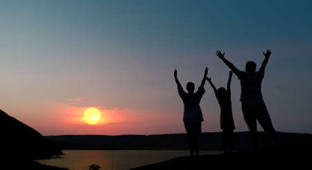 hands lifted: The family from three persons welcomes the sunset sun. Stock Photo