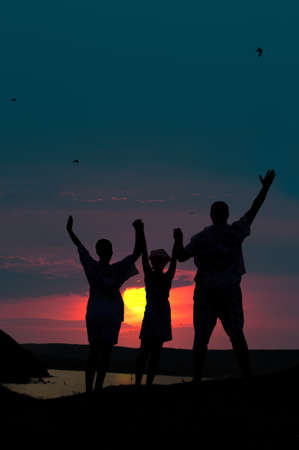 lifted hands: The family from three persons welcomes the sunset sun. Stock Photo