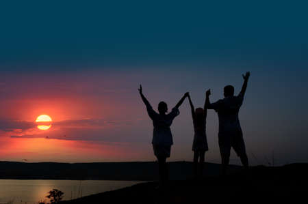 hand lifted: The family from three persons welcomes the sunset sun. Stock Photo