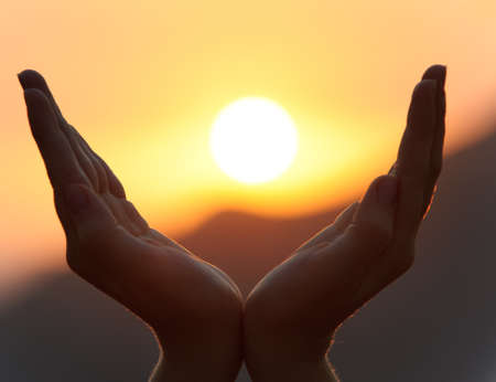 Decline in hands. A sunset on a background of the lifted female hands