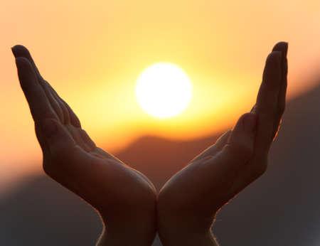 REZANDO: Disminución de las manos. Una puesta de sol sobre un fondo de las manos levantadas femenino