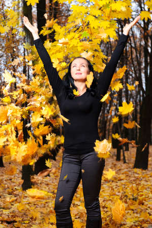 throw up: The women with the lifted hands autumn forest. Falling yellow leaf Stock Photo