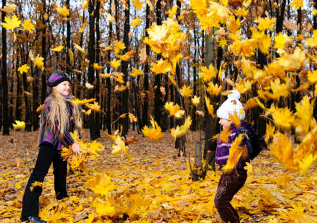 fall fun: Children in autumn forest. Play fallen down leaf