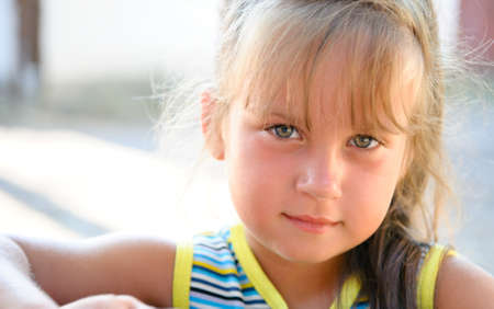 light brown eyes: Portrait of the little girl close up. Outdoors