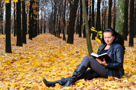 The attractive woman reads the book in autumn forest. photo