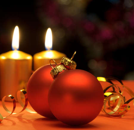 candlelight: Christmas candles and red spheres. A celebratory composition