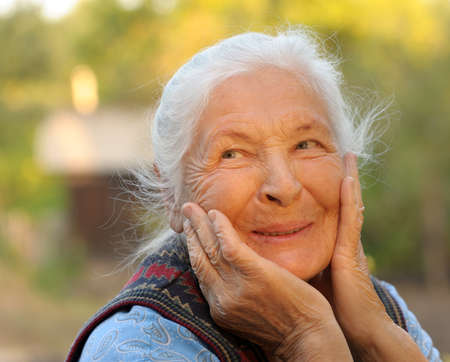 Portrait of the laughing elderly woman. A photo on outdoors photo