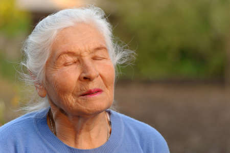 one year old: The elderly woman with closed eyes. A photo outdoors