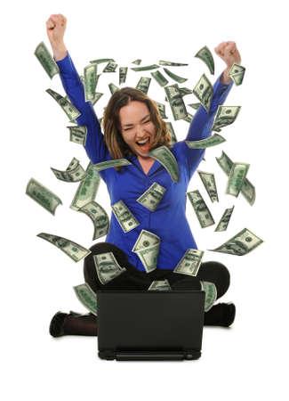 euphoric: La donna di fronte il portatile con fly dollari. Esso � isolato su uno sfondo bianco Archivio Fotografico