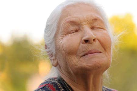 closed eyes: De bejaarde vrouw met gesloten ogen. Een foto buiten